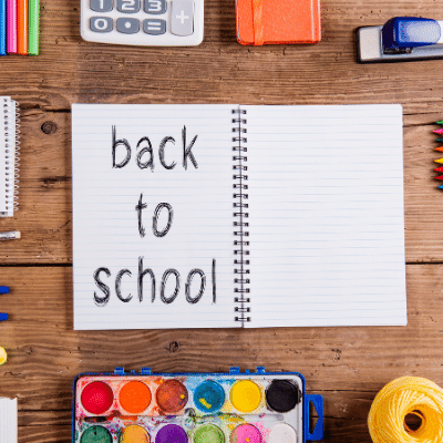 """The traditions of the first day. inlingua Andorra blog post notebook with the words """"back to school"""" scribbled on it surrounded by calculator, colors and a stabler on a desk."""