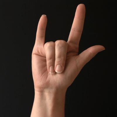 "El llenguatge en el dia blogpost ""hand sign"" for ""I love you"" with black background"