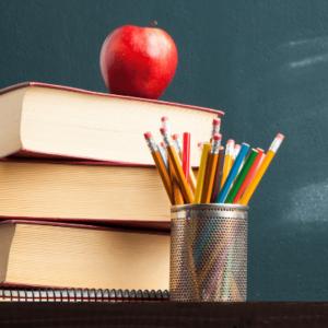 Apple con libros y lápices delante de una pizarra en el aula inlingua andorra