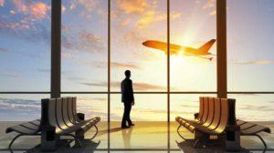L'homme à l'aéroport en regardant un avion décoller à travers une fenêtre inlingua Andorra Travel and Tourism Class