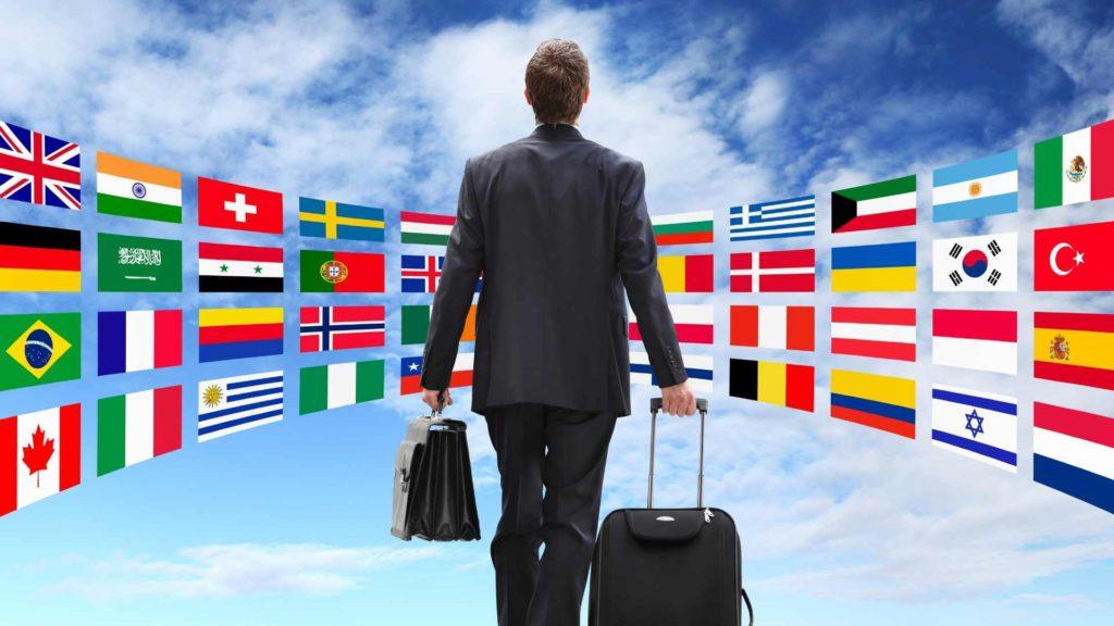 Étudiant inlingua Andorra apprenant de nouvelles langues en Andorre et voyageant à l'étranger. Homme avec valise devant de nombreux drapeaux différents