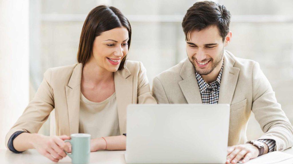 Jeunes étudiants inlingua Andorre (femme et homme) sur ordinateur portable apprentissage des langues en ligne