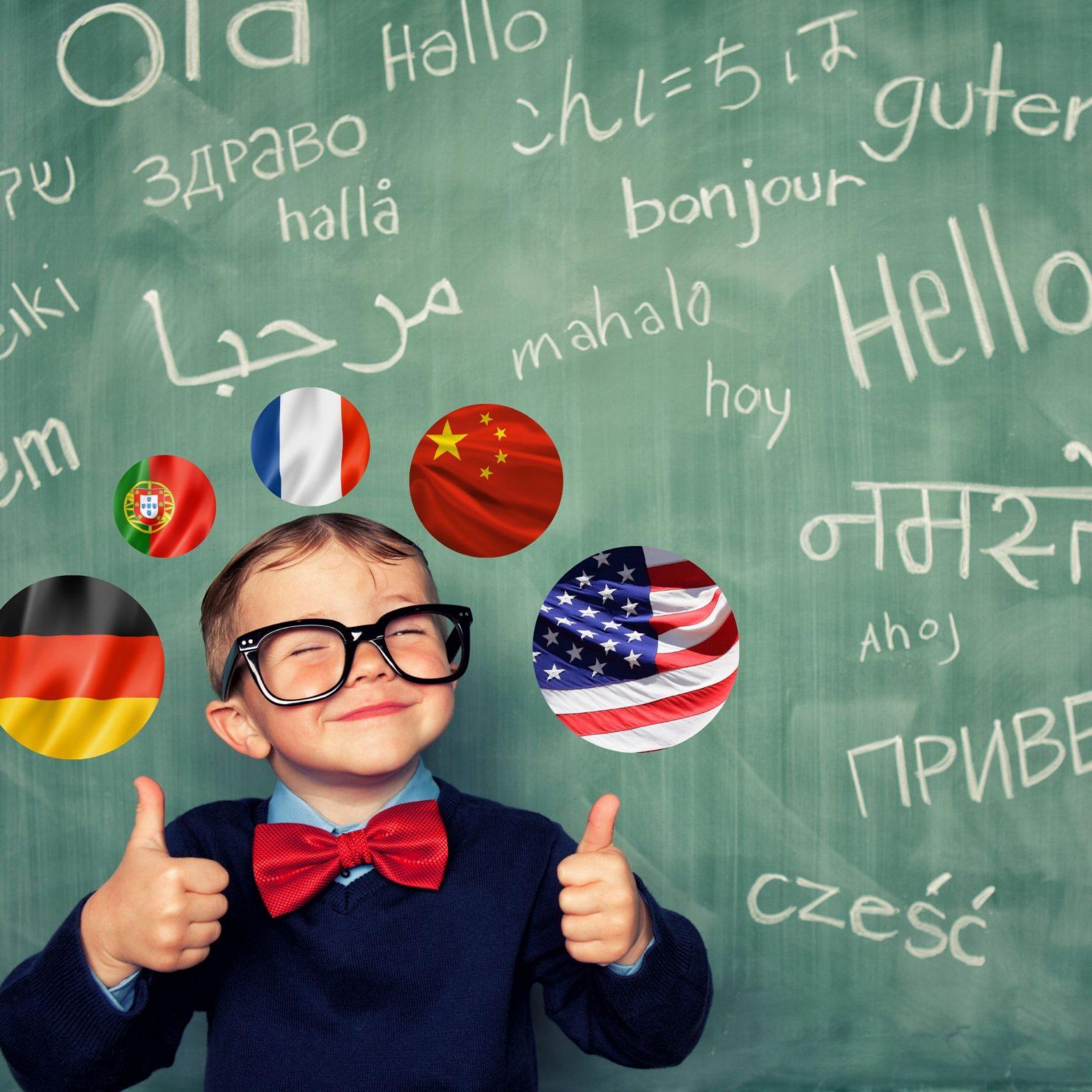 Nen petit amb ulleres davant d'una pissarra amb paraules en diferents idiomes amb banderes alemanyes, portugueses, franceses, xineses i americanes al voltant del cap. El nen petit dóna dos polzes i somriu.