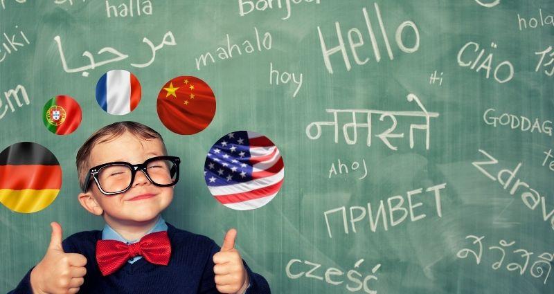 Nen petit somrient amb diferents banderes al cap. Davant d'una pissarra amb paraules diferents en diferents idiomes mentre sosté dos polzes cap amunt.