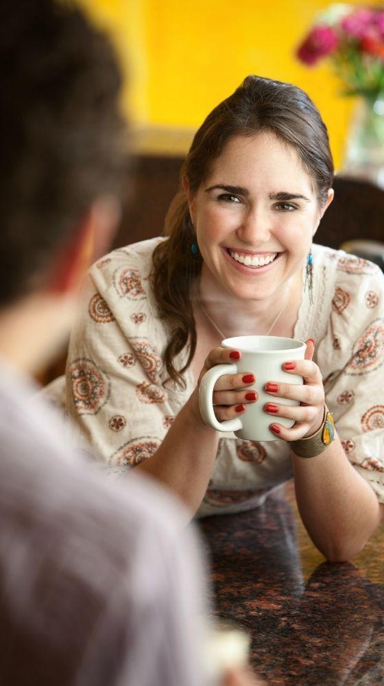 Dona que sosté una tassa de cafè, inclinada mentre escolta la seva amiga parlar