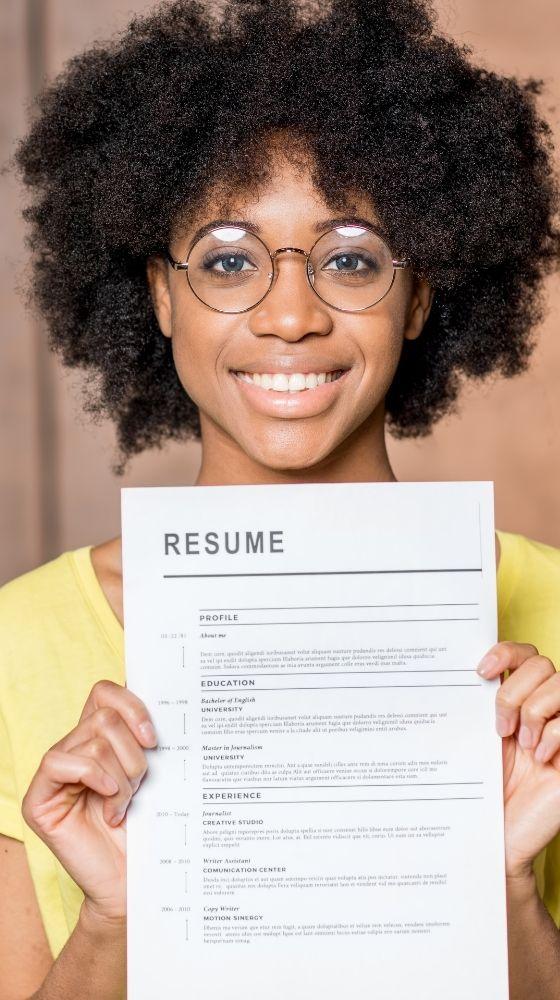 Dona amb ulleres somrient mentre sosté el seu currículum